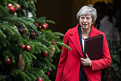 London, UK. 4th December, 2018. Prime Minister Theresa May glances at the Christmas tree as she leaves 10 Downing Street for the House of Commons to open the debate on the final Brexit deal.