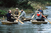 men sailing traditional hand made coracles on river