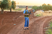 A member of the Free Syrian Army (FSA) is seen standing as he holds his Kollashnikov AK47 rifle around the military strategic position nearby the target ahead of a military operation in Minaq (Menagh) military airport on Friday, Jun 29, 2012. (Photo by Vudi Xhymshiti)