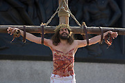 The final scenes of a suffering Jesus being crucified on the cross at the base of Nelsons Column during The Passion of Jesus which is performed in Londons Trafalgar Square by members of Wintershall Trust on London, 25th March 2016: Played annually on Good Friday it celebrates the cruxifixion and resurrection of Jesus Christ. The cast re-enacts the Christian Biblical story to an audience of thousands and the main character is played by professional actor James Burke-Dunsmore. .