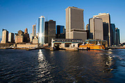 A Staten Island Ferry waits in the Whitehall Terminal in Lower Manhattan, New York City, New York, United States of America. Sunlight reflects off 17 State Street building in the heart of the Financial District of Manhattan and famous for its distinct curved facade.