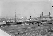 """1205-G06. """"Portland dock & ships"""" Portland harbor viewed from the east side of the original Burnside bridge. Steel and Broadway bridges on right. Albina rail yards in foreground. Photo by K Brown"""