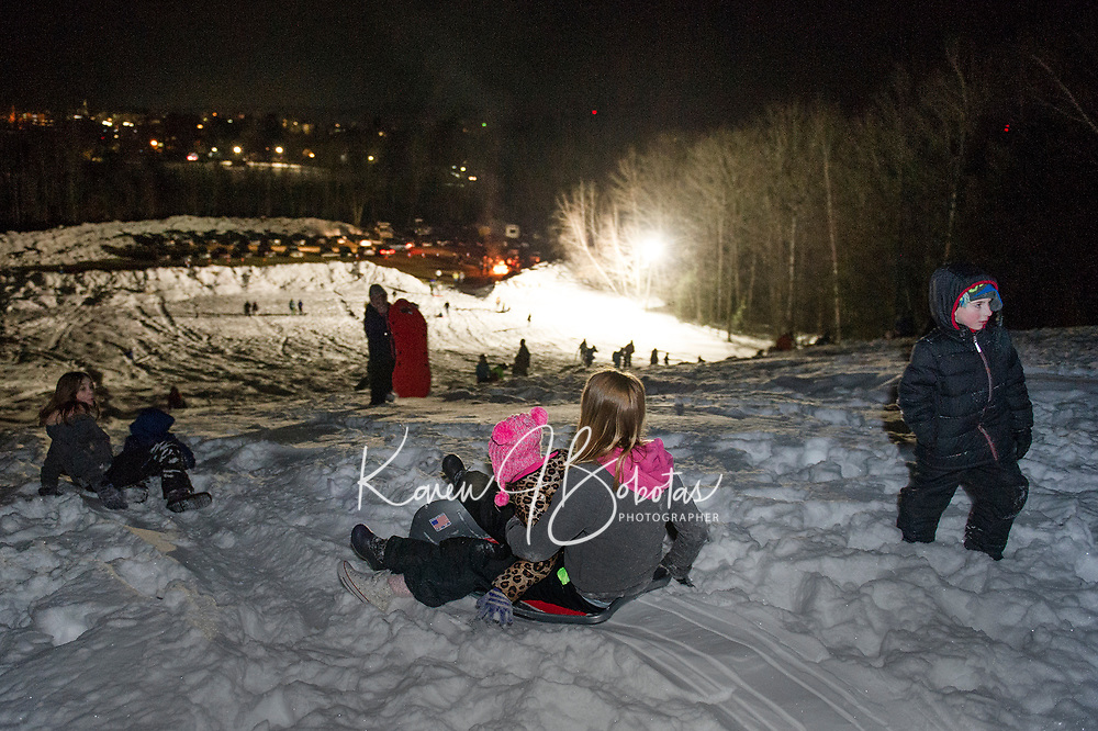 MacKenzie and Kayla hop on a sled together at the top of Memorial Hill during Laconia Parks and Rec Sledding Party Friday evening.  (Karen Bobotas/for the Laconia Daily Sun)