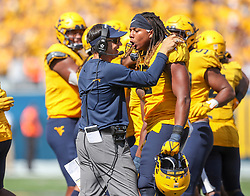 Sep 18, 2021; Morgantown, West Virginia, USA; West Virginia Mountaineers head coach Neal Brown celebrates with West Virginia Mountaineers defensive lineman Taijh Alston (12) following a turnover during the fourth quarter against the Virginia Tech Hokies at Mountaineer Field at Milan Puskar Stadium. Mandatory Credit: Ben Queen-USA TODAY Sports