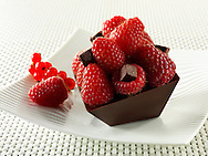 A modern square chocolate cake filled with chocolate truffle and topped with fresh raspberries