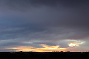 dramatic sunrise contrasting with a silhouette hilly landscape