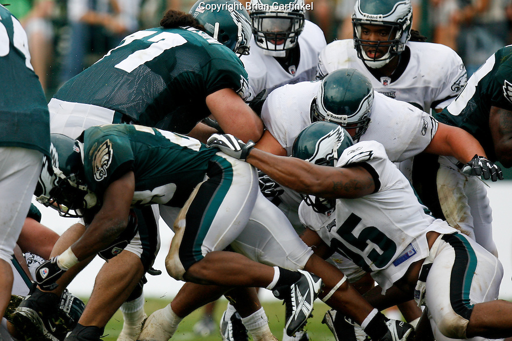 Bethlehem, Pennsylvania - Lorenzo Booker carries the ball and is pulled down by Jerome Mcdougle  at the Eagles Training camp at Lehigh University.