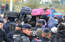 """A group of men with suitcases in a large queue of migrants outside a processing centre in """"the jungle"""" near Calais, northern France, as the mass exodus from the migrant camp begins."""