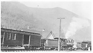 """Rear engineer's-side view of an RGS C-16 ready to depart Telluride northbound with the #6 passenger train.  Another passenger train is ahead where two ladies are exchanging greetings.<br /> RGS  Telluride, CO  Taken by Virden, Walter - ca. 1920-1929<br /> In book """"Rio Grande Southern, The: An Ultimate Pictorial Study"""" page 87<br /> Also at RD131-049 and RD155-098.  Also in """"RGS Story Vol. II"""", p. 93.<br /> Thanks to Don Bergman for additional information."""