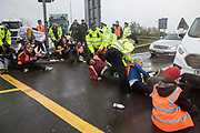 Metropolitan Police officers remove Insulate Britain climate activists from a M25 slip road at Junction 14 close to Heathrow airport which they had blocked as part of a campaign intended to push the UK government to make significant legislative change to start lowering emissions on 27th September 2021 in Colnbrook, United Kingdom. The activists are demanding that the government immediately promises both to fully fund and ensure the insulation of all social housing in Britain by 2025 and to produce within four months a legally binding national plan to fully fund and ensure the full low-energy and low-carbon whole-house retrofit, with no externalised costs, of all homes in Britain by 2030.