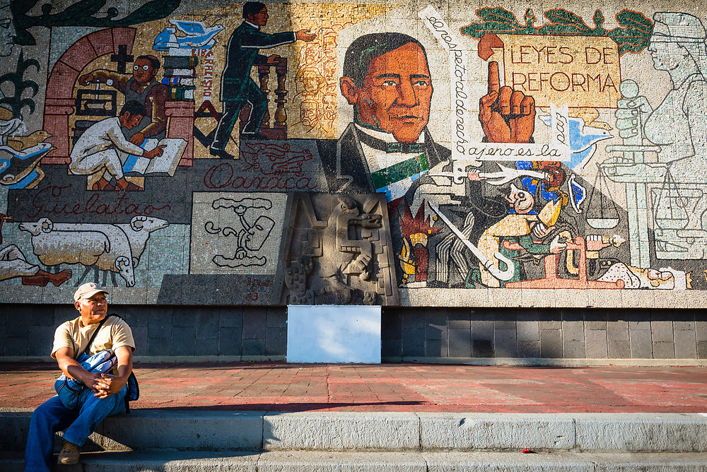 Man sitting in front of a mural paying tribute to Benito Juarez in Oaxaca, Mexico