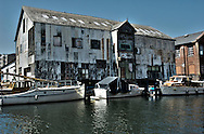 An old warehouse on a river with moored boats