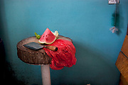 Watermelon, a red plastic bag and a meat cleaver on a table for chopping at a poor home in De Hui city, Jilin Province. North Eastern China.