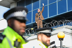 © Licensed to London News Pictures. 10/10/2019. London, UK. An Extinction Rebellion protester breaks on to the roof at London City Airport. Protesters plan to occupy the terminal building in a 'Hong Kong-style' shutdown as part of ongoing protests calling on government departments to tackle the Climate Emergency. Photo credit: Rob Pinney/LNP