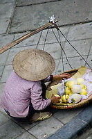 Street vendors wearing conical hats selling all kinds of fresh produce can be found on the streets of the old quarter in Hanoi.