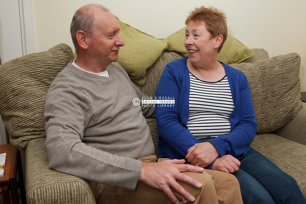 Couple relaxing on sofa. Cleared for Mental Health issues.
