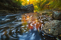 A long exposure reders an swirling abstratct pattern of bubbles and autumn leaves amid a wash of reflected color on Duck Brook in Acadia National Park, Maine, USA.