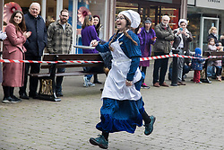 Windsor, UK. 25 February, 2020. Competitors from local businesses dressed around a theme of a 15th century housewife show off their flipping skills and fancy footwork as they compete on Shrove Tuesday in the Windsor and Eton Flippin' Pancake Challenge in aid of Alexander Devine Children's Hospice Service.