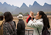 Tourist take photographs as she travels by boat along Li River between Guilin and Yangshuo, China