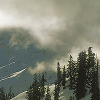 Clouds drift past snow-covered slopes under Mount Shuksan.