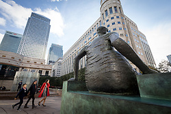 © Licensed to London News Pictures. 25/10/2017. LONDON, UK.  Henry Moore's sculpture, Draped Seated Woman 1957, affectionately known as 'Old Flo' is installed in Cabot Square, Canary Wharf, east London after 20 years on public display at the Yorkshire Sculpture park. The iconic sculpture was loaned to Yorkshire by the London Borough of Tower Hamlets in 1997, after the Stifford Estate in Stepney where it had been located since 1962 was demolished. The return of the sculpture to London marks an end to a bitter political battle over Old Flo. In 2012 the disgraced former mayor of Tower Hamlets Lutfur Rahman, declared that it should be sold to raise £20m, that sparked protests & a court battle over who actually owned the sculpture. Tower Hamlets was confirmed as the legal owner in 2015.  Photo credit: Vickie Flores/LNP