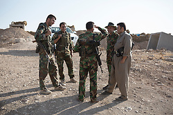 © Licensed to London News Pictures. 01/09/2015. Bashiqa, Iraq. Kurdish peshmerga chat between guard shifts at a defensive positon on the top of Bashiqa Mountain near Mosul, Iraq.<br /> <br /> Bashiqa Mountain, towering over the town of the same name, is now a heavily fortified front line. Kurdish peshmerga, having withdrawn to the mountain after the August 2014 ISIS offensive, now watch over Islamic State held territory from their sandbagged high-ground positions. Regular exchanges of fire take place between the Kurds and the Islamic militants with the occupied Iraqi city of Mosul forming the backdrop.<br /> <br /> The town of Bashiqa, a formerly mixed town that had a population of Yazidi, Kurd, Arab and Shabak, now lies empty apart from insurgents. Along with several other urban sprawls the town forms one of the gateways to Iraq's second largest city that will need to be dealt with should the Kurds be called to advance on Mosul. Photo credit: Matt Cetti-Roberts/LNP