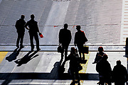 Silhouettes of people waiting on a train station platform. Photographed in Alexandroupoli, Greece