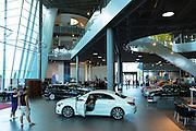 Prospective buyer inspecting a Mercedes CLA 180 Saloon in Mercedes-Benz showroom in Stuttgart, Bavaria, Germany