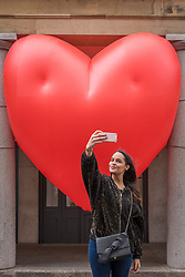"""© Licensed to London News Pictures. 14/02/2018. LONDON, UK. A tourist takes a selfie against a giant chubby heart balloon at Covent Garden as part of """"Chubby Hearts Over London"""",  a design project conceived by Anya Hindmarch.  Supported by the Mayor of London, the British Fashion Council and the City of Westminster giant chubby heart balloons will be suspended over (and sometimes squashed within) London landmarks as a declaration of love to the city starting on Valentine's Day and continuing throughout London Fashion Week.   Photo credit: Stephen Chung/LNP"""