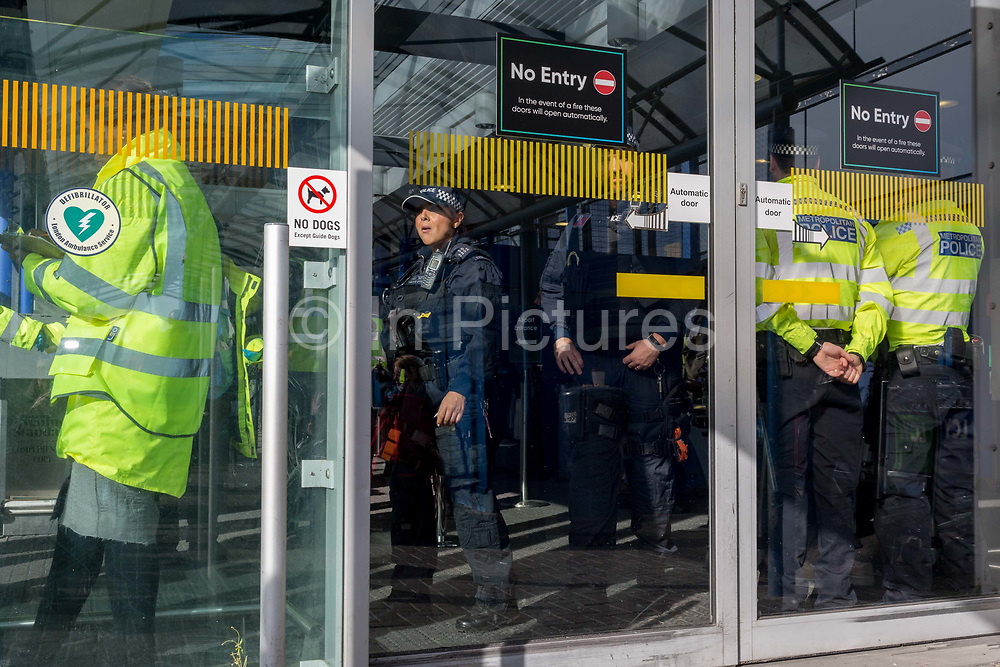As environmental activists protest about Climate Change, police officers secure the terminal building during the occupation of City Airport Londons Business Travel hub in east London, the fourth day of a two-week prolonged worldwide protest by members of Extinction Rebellion, on 10th October 2019, in London, England.