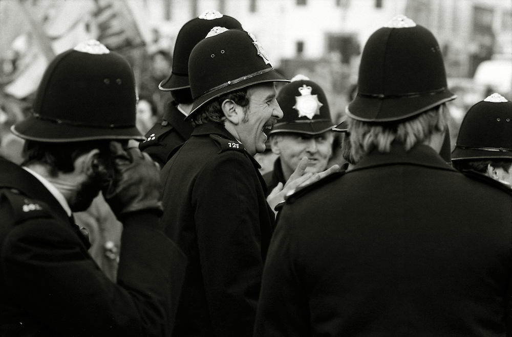 Policemen at a demonstration in London in 1984 share a joke.