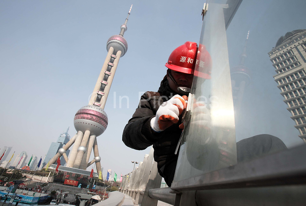 Construction workers operate on a site to install glass in front of the Pearl Oriental Tower in Shanghai, China on 18 December, 2009. Shanghai is on its way of becoming one of the world's most important financial centers.