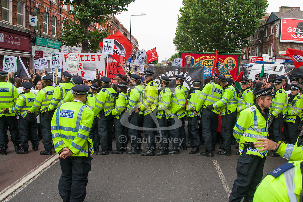 """Cricklewood, London, July 19th 2014. Large numbers of police were required to keep scores of anti-fascist counter-protesters separate from 13 """"South East Alliance""""  far right anti-Islamists, demonstrating near the London offices of Egypt's Muslim Brotherhood,"""