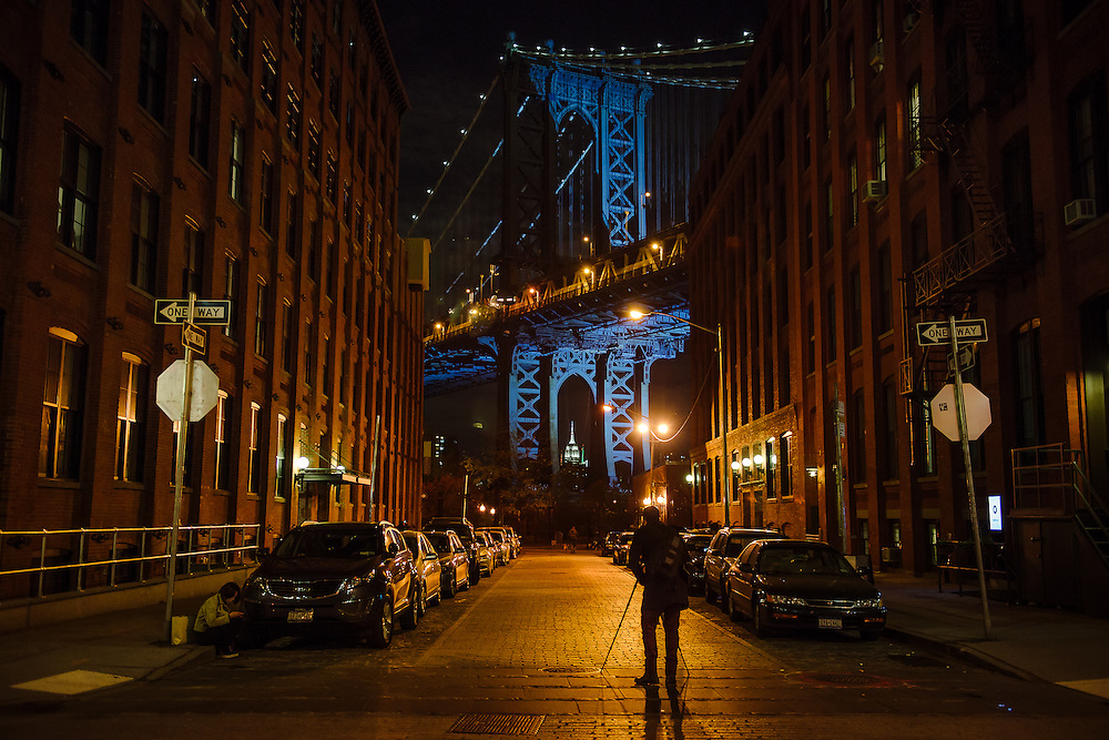 A photographer stands in the middle of Washington Street in DUMBO, Brooklyn on a night when the Manhattan Bridge is unusually  lit.