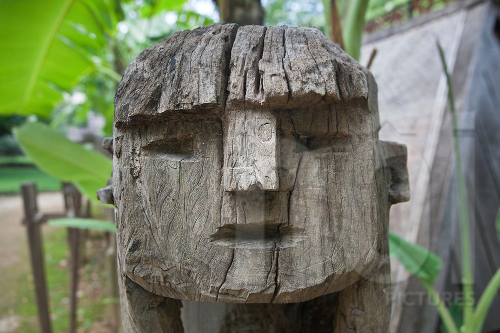 Close up of a statue's face carved in a piece of wood and placed in front of a Jarai (Gia Rai) ethnic's tomb. Ethonology museum, hanoi, vietnam, Asia.