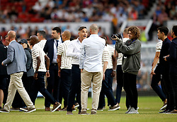 England's Robbie Williams (centre left) with World XI's Eric Cantona (centre right) prior to the UNICEF Soccer Aid match at Old Trafford, Manchester.