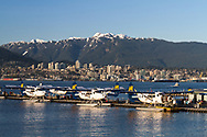 Seaplanes at the Vancouver Harbour Flight Center at Coal Harbour in Vancouver, British Columbia, Canada.  The Vancouver Harbour Flight Centre was previously known as the Vancouver Harbour Water Airport or the Coal Harbour Seaplane Base. The City of North Vancouver and Mount Seymour can be seen in the background.