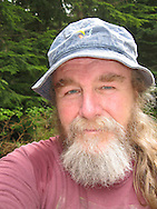 A senior blue-eyed bearded man with a blue bucket hat looks pensively at the camera.