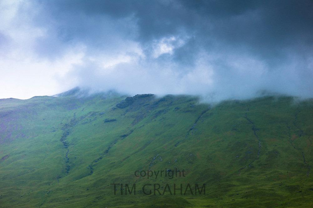Low dark grey clouds tumbling over mountains on Isle of Mull in the Inner Hebrides and Western Isles, West Coast of Scotland