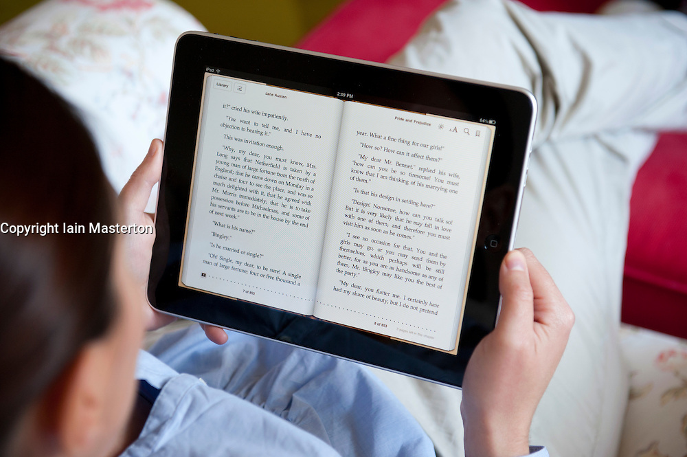 Woman using iPad tablet computer to read eBook from iBook store
