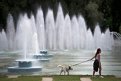 © Licensed to London News Pictures. 10/06/2021. London, UK. A woman walks her dog in front of the fountains at Battersea Park in south London on another warm summer day. . Photo credit: Ben Cawthra/LNP