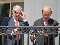 United States Attorney General Jeff Sessions, left, and US Secretary of Commerce Wilbur Ross, right, check their electronic devices as they look at the partial eclipse of the sun from the Blue Room Balcony of the White House in Washington, DC on Monday, August 21, 2017.<br /> Credit: Ron Sachs / CNP