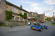Kit car passes the village shop in Muker in Swaledale, which runs broadly from west to east. To the south and east of the ridge a number of smaller dales. Swaledale is a typical limestone Yorkshire dale, with its narrow valley-bottom road. Yorkshire, England, UK.