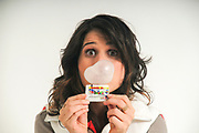 young woman blows a bubble with pink bubble gum while holding the cartoon from Bazooka Chewing Gum