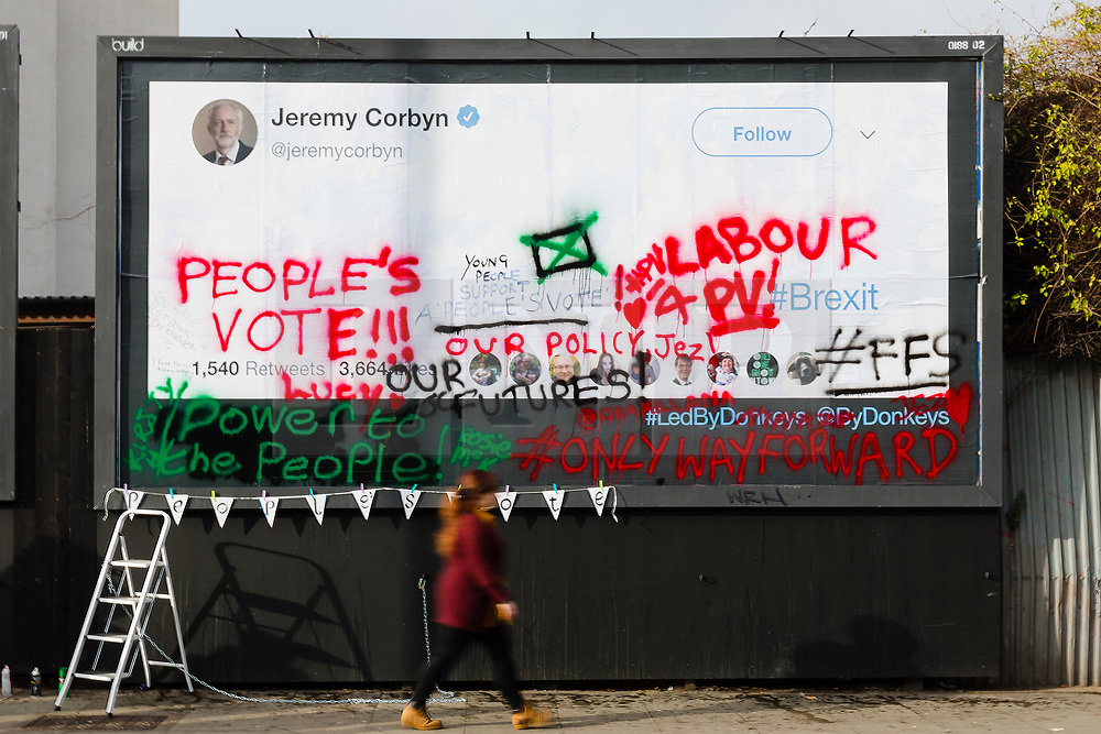 © Licensed to London News Pictures. 12/02/2019. London, UK.  A woman walks past after young anti-Brexit campaigners from the For our Future's Sake (FFS) wing of the People's Vote campaign in collaboration with the Led By Donkeys campaign wrote messages on a large billboard in Islington, stating why they want Jeremy Corbyn, the leader of the Labour Party to back a People's Vote on Brexit. The billboard, located in the Islington North constituency of Mr Corbyn shows messages reminding him that a majority of young Labour supporters want a public vote or second referendum on Brexit. Photo credit: Vickie Flores/LNP