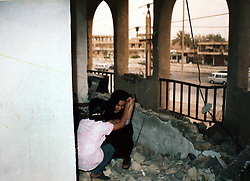 Photograph of Amira Khalid, 44, wife of Salah Izat, 51, as she tries to recover items from their home which burnt down last year, Baghdad, Iraq, March 2, 2004. Salah Izat's home was destroyed in March 2003 when an American missile hit just outside their front door. A year later, Izat is getting better pay wages, but has lost his right leg from diabetes. He says the lack of medical resources after the war made him unable to get proper attention for his ailing leg, possibly being the reason it became so gangrenous that it had to be amputated.