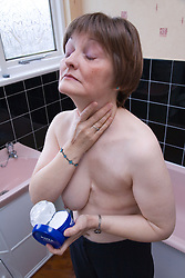 Woman who has had a mastectomy; the removal of a breast in response to breast cancer; applying face cream in her bathroom,