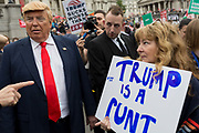 On US President Donald Trumps second day of a controversial three-day state visit to the UK, a Trump lookalike engages with protesters voicing their opposition to the 45th American President, in Trafalgar Square, on 4th June 2019, in London England.