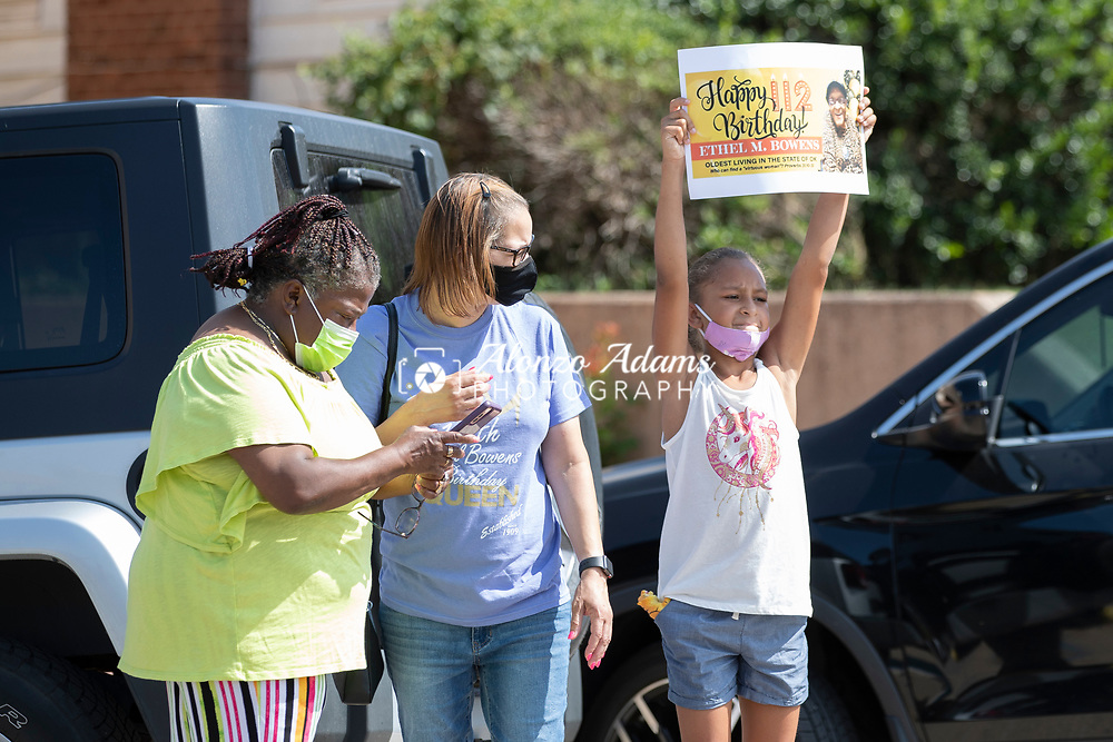 A young girl holds up a sign during a parade for Ethel M. Bowens in Guthrie, Okla. on Saturday, Aug. 21, 2021. Photo by Alonzo J. Adams.