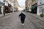 According to the governments Covid social distance restrictions, shops and retail spaces remain closed as an elderly lady walks unsteadily with the use of walking sticks towards Covent Garden during the third lockdown of the Coronavirus pandemic, on 3rd February 2021, in London, England.